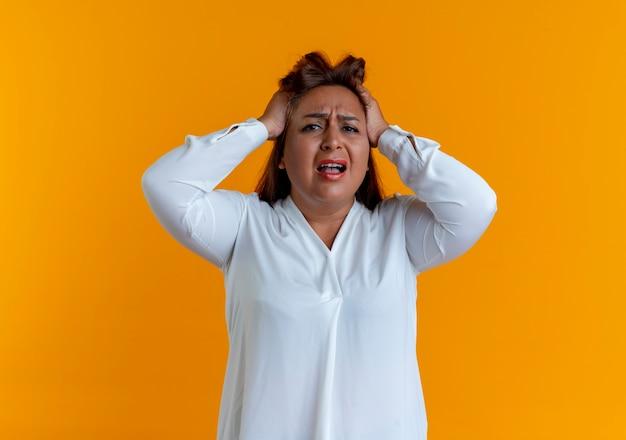 La donna di mezza età caucasica casuale triste ha afferrato la testa isolata sulla parete gialla