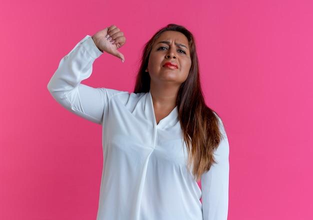Donna di mezza età caucasica casuale triste il suo pollice giù sul colore rosa