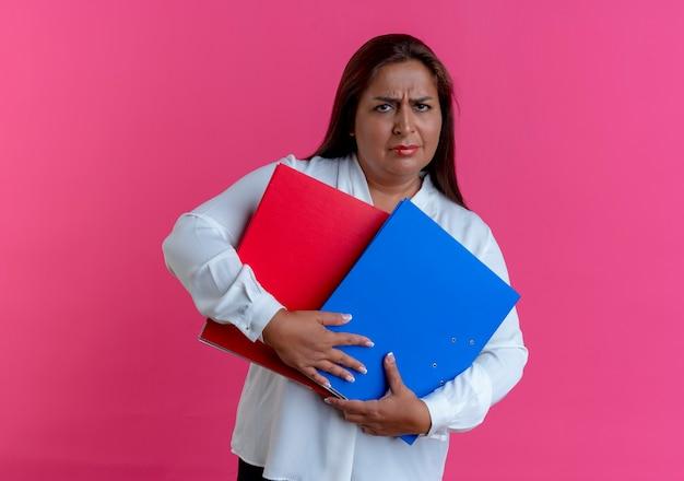 Donna di mezza età caucasica casuale triste che tiene le cartelle sul rosa