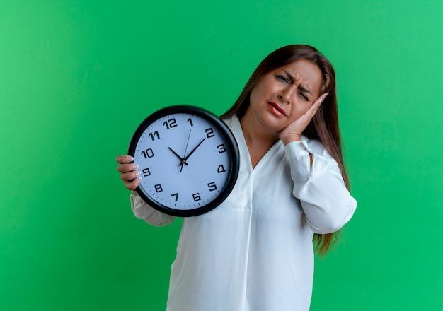Donna di mezza età caucasica casuale triste che tiene l'orologio di parete e che mette la mano sulla guancia isolata sulla parete verde