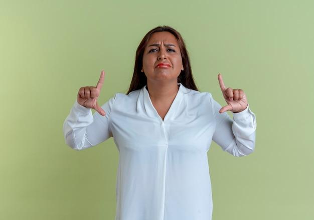 Грустная случайная кавказская женщина средних лет, показывающая размер, изолирована на оливково-зеленой стене