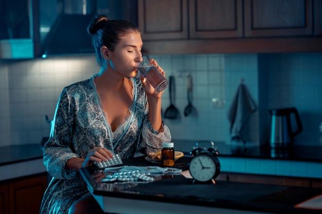 夜に彼女の台所に座って、コップ一杯の水で薬を飲む悲しい白人女性