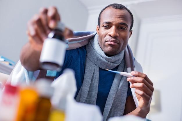 薬と一緒にボトルを見て、温度計を持って病気について考える悲しい元気のない大人の男