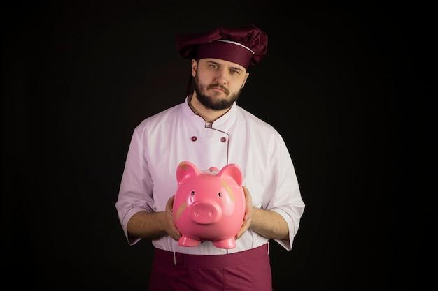 Грустный повар мужчина в форме держит сломанную розовую копилку с лейкопластырем