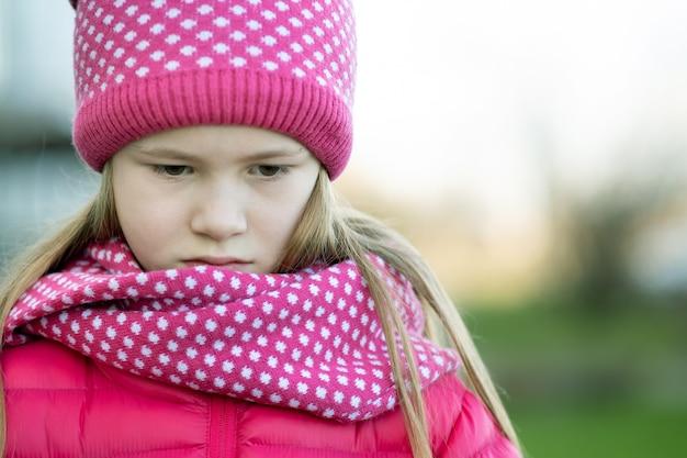 屋外の暖かいニット冬服で悲しい子少女。