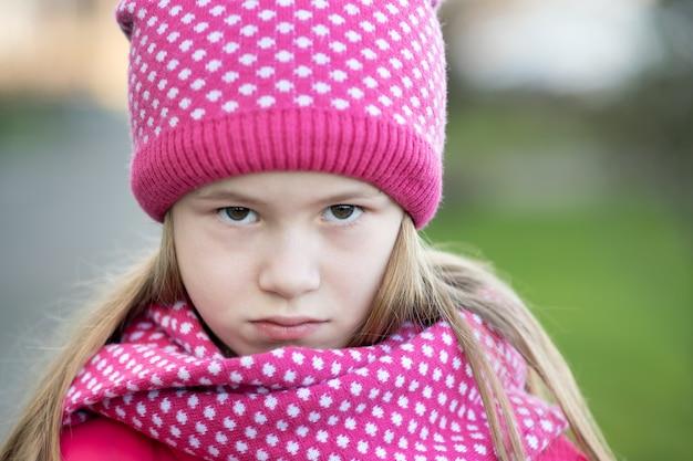Грустная детская девочка в теплой вязаной зимней одежде на открытом воздухе.