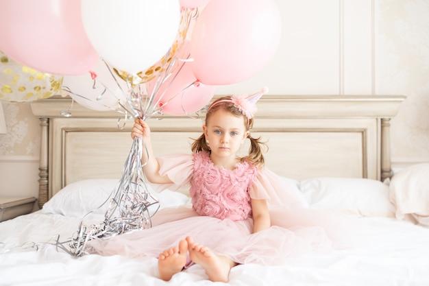 ベッドに座っている悲しい子供の女の子は、誕生日のために動揺して憤慨している子供を風船の束を保持