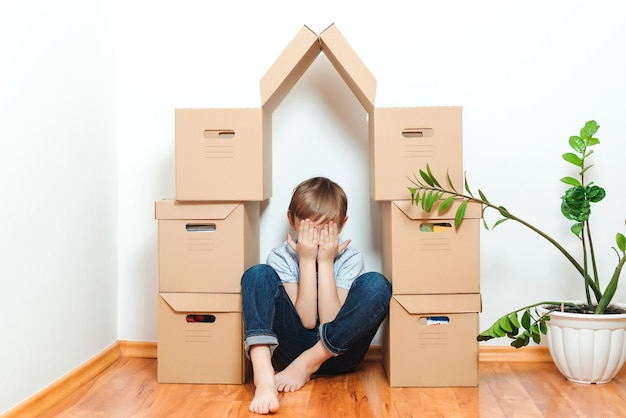 Sad child hiding in house making from boxes. mortgage, people, housing, moving and real estate.