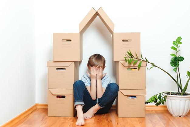 Печальный ребенок прячется в доме из коробок. ипотека, люди, жилье, переезд и недвижимость.