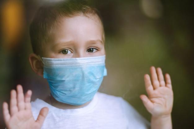 医療用マスクの悲しい子供が窓の外を見る家にいる