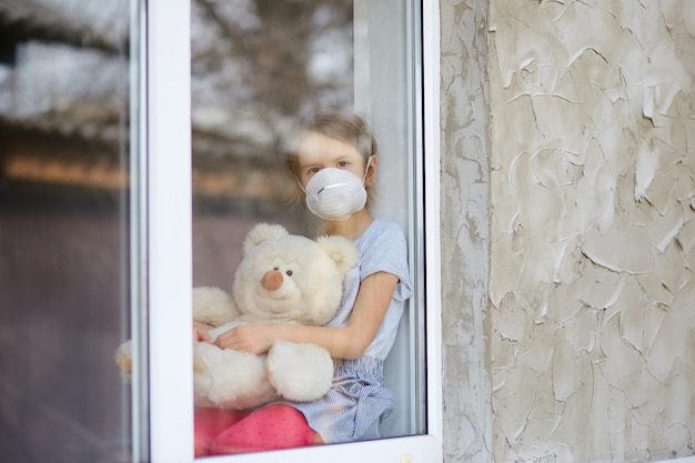 Sad child, little girl in mask  with teddy bear looking from window, coronavirus quarantine, home school. view from street. stay at home. concept of coronavirus