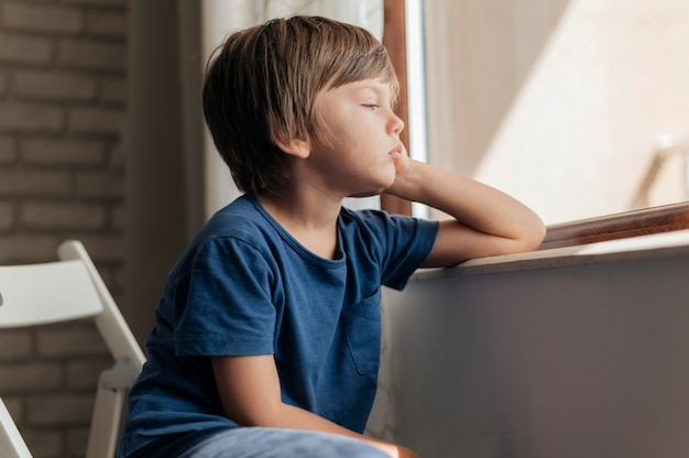 Bambino triste che guarda attraverso la finestra durante la quarantena