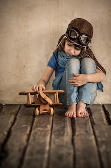 Sad child playing with toy wooden airplane