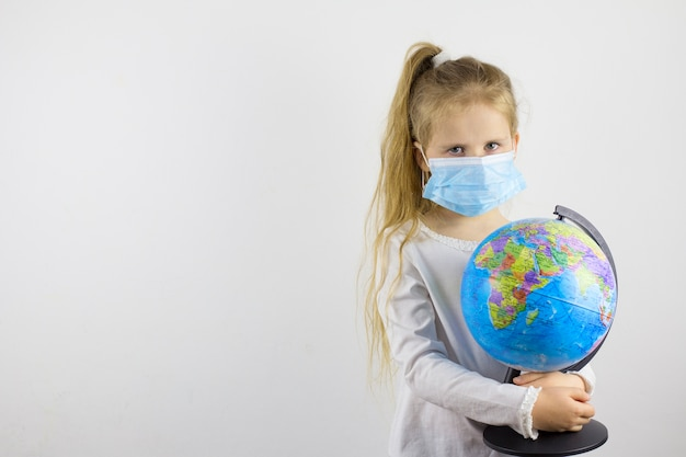 A sad child in a protective mask and holds a globe. the concept of isolating the world from a new generation virus