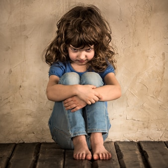 暗い部屋の床に座っている悲しい子供