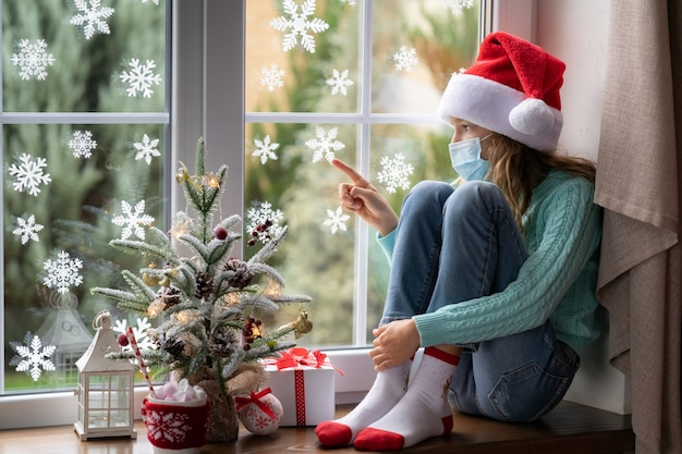 Sad child stay at home in christmas time. winter holiday during pandemic coronavirus covid 19 concept
