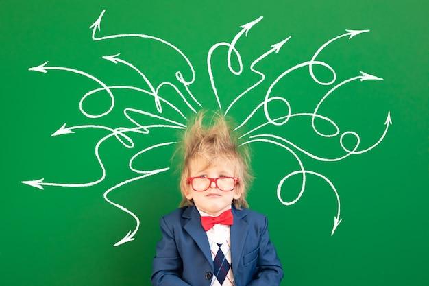 Унылый ребенок-студент в классе против зеленой доски.