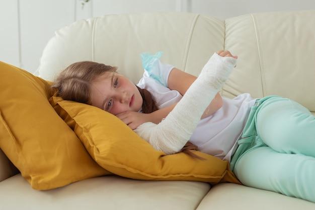 Печальный ребенок с гипсом на сломанном запястье или руке, лежащий на диване, концепция выздоровления и болезни