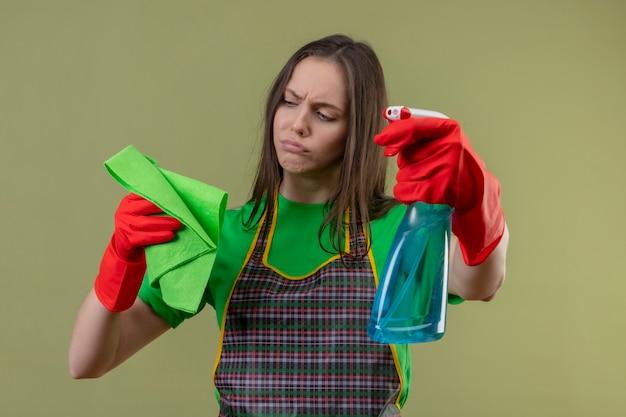 Ragazza triste di pulizia che indossa l'uniforme in guanti rossi che tengono spray di pulizia guardando straccio sulla sua mano su sfondo verde isolato