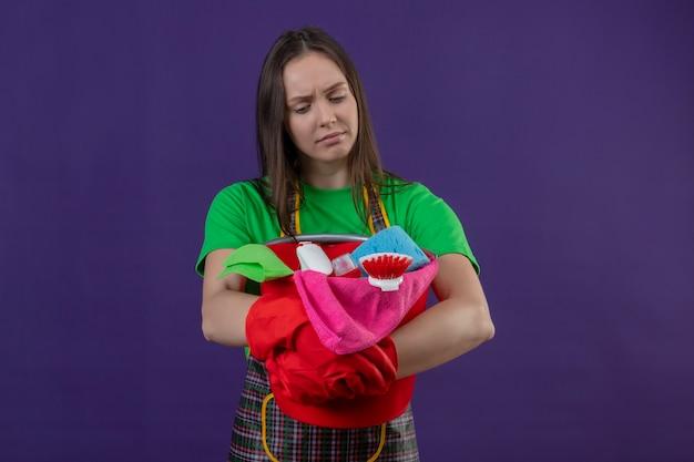 Ragazza triste di pulizia che indossa l'uniforme in guanti rossi che tengono strumenti di pulizia su fondo viola isolato