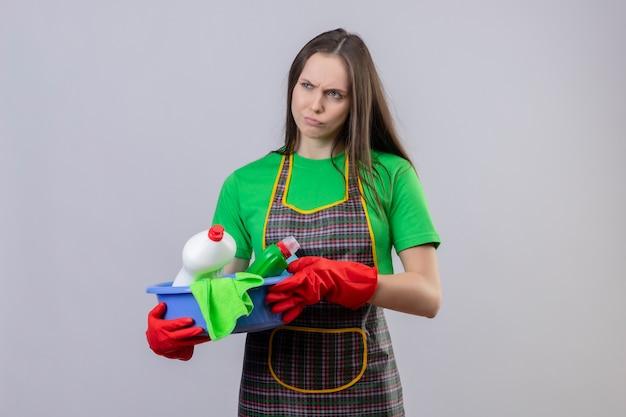 Ragazza triste di pulizia che indossa l'uniforme in guanti rossi che tengono gli strumenti di pulizia su fondo bianco isolato