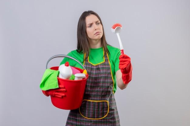 Ragazza triste di pulizia che indossa l'uniforme in guanti rossi che tengono gli strumenti di pulizia e che cercano la spazzola di pulizia sulla sua mano su fondo bianco isolato