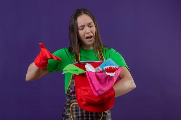 La ragazza triste di pulizia che porta l'uniforme in guanti rossi indica gli strumenti di pulizia sulla sua mano su fondo viola isolato