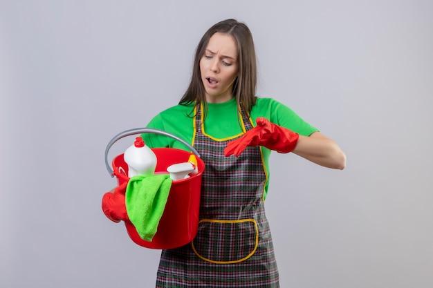 La ragazza triste di pulizia che porta l'uniforme in guanti rossi indica gli strumenti di pulizia sulla sua mano su fondo bianco isolato