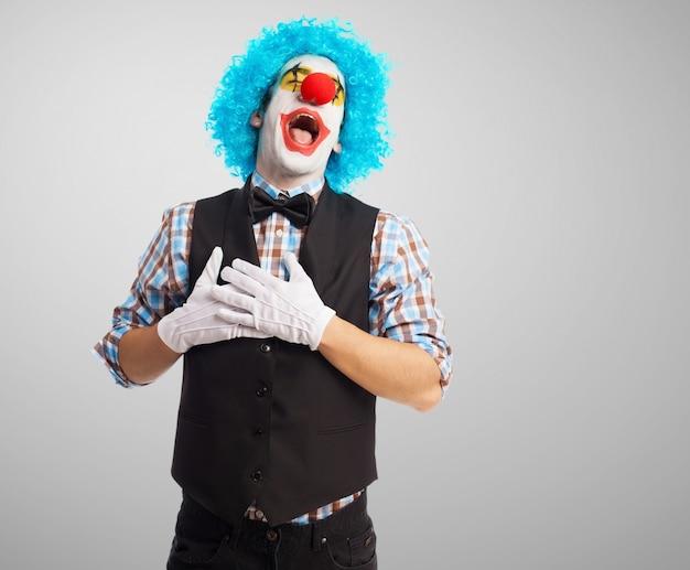 Грустный клоун, держась за руки на грудь