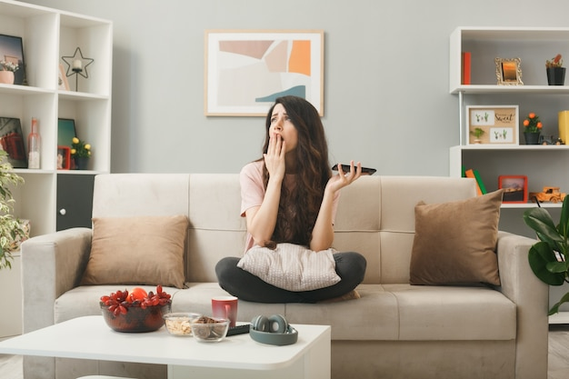 Sad cofered face with hand young girl holding phone sitting on sofa behind coffee table in living room