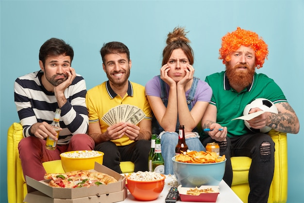 Sad company of friends feel bored as watch not interesting match on television, surrounded with different delicious snacks