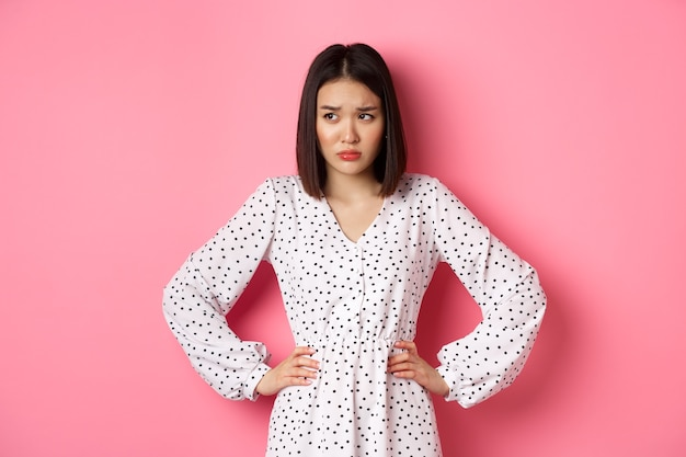 Sad and concerned asian woman having problem, holding hands on waist and looking left with upset face, standing in dress against pink background