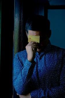Печальный запутанный и стрессовый человек, держащий кредитные карты.