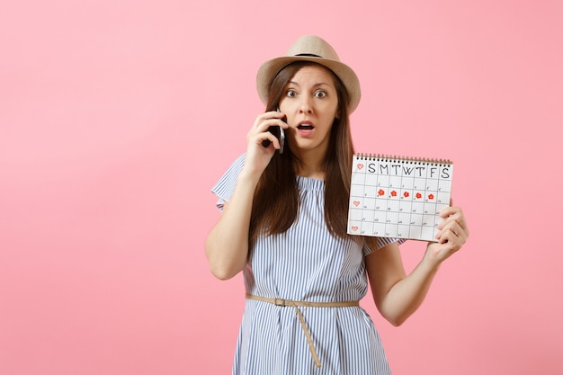 Sad confused woman talking on mobile phone, holding periods calendar for checking menstruation days isolated on bright trending pink background. medical, healthcare, gynecological concept. copy space.