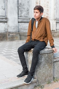 Sad contemplated teenage boy with shoulder bag sitting on wall