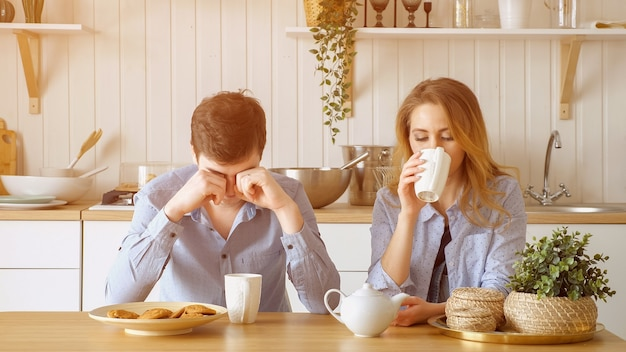 Sad couple blonde girl and guy have breakfast drinking tea with biscuits silently and man yawns at table in kitchen, sunlight