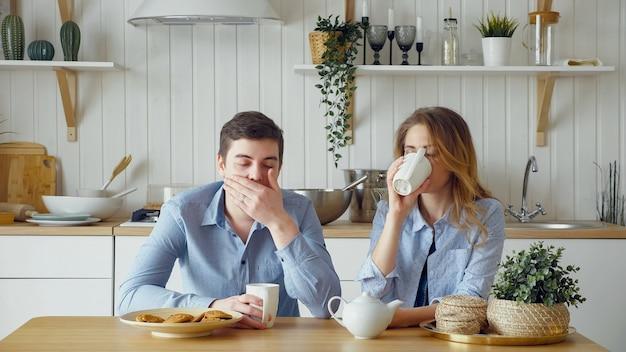 Sad couple girl guy have breakfast drinking tea silently