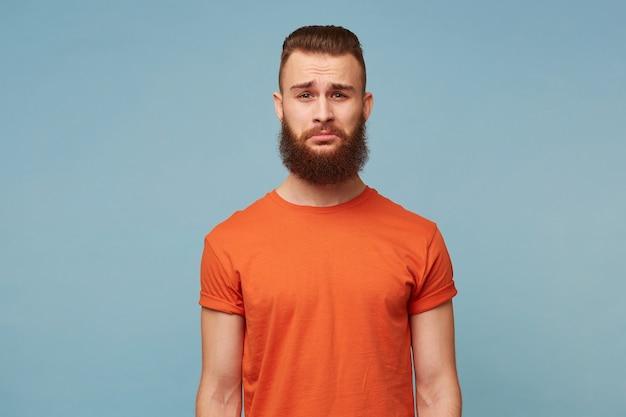 Грустный плачущий бородатый парень в красной футболке, изолированной на синем, чувствует себя расстроенным