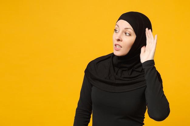 히잡 검은 옷을 입고 슬픈 우는 혼란 된 젊은 아라비아 무슬림 여성이 노란색 벽 초상화에 고립 된 소리를 듣습니다. 사람들이 종교 이슬람 라이프 스타일 개념.
