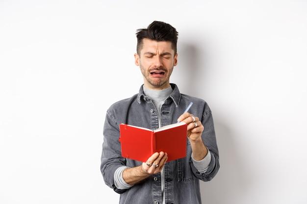 비참한 얼굴로 일기에 쓰는 슬픈 우는 남자는 흰색 배경에 서있는 일기 나 플래너에 메모를 작성하는 동안 괴로워합니다.