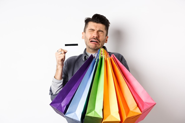 Sad crying man wasted all money on shopping, holding bags and showing empty credit card, standing against white background.