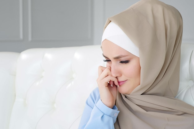 ヒジャーブで悲しい泣いているイスラム教徒の女性が自宅のソファに座っています。