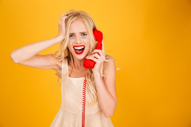 Sad crying screaming young blonde woman talking by telephone.