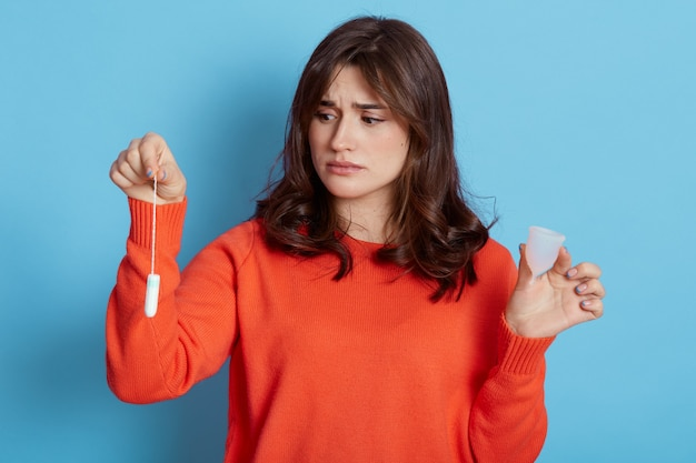 손에 들고 오렌지 스웨터를 입고 슬픈 검은 머리 여성 여성 위생 제품