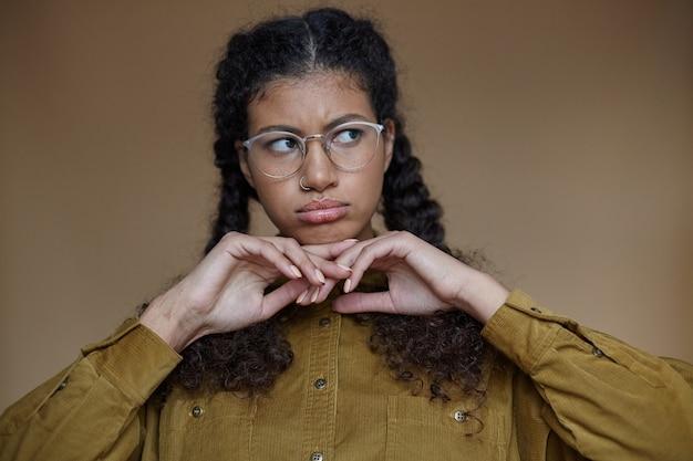 眼鏡をかけ、上げられた手にあごを持って、動揺した顔と折り畳まれた唇で脇を見て、孤立した編みこみの髪型を持つ悲しい暗い肌の巻き毛の女性