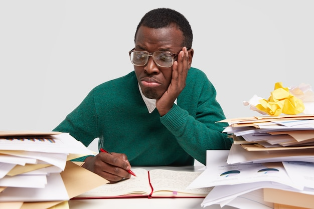 Sad dark skinned male hipster feels overworked, overloaded, notes ideas in notebook, purses lips in displeasure, wears big square glasses for good vision