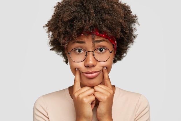 슬픈 어두운 피부를 가진 여자가 웃는 척하고 두 검지 손가락을 입술 근처에 유지하고 미소를 짓습니다.