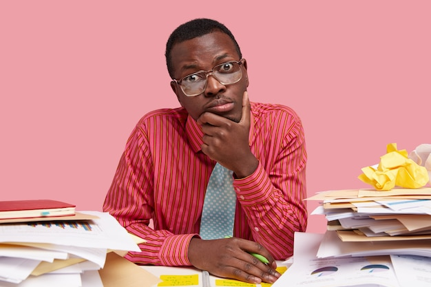 Sad dark skinned young man holds chin, looks thoughtfully , dressed in formal clothes, holds pen, makes records in notepad