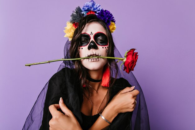 Triste sposa morta in velo nero in posa di halloween. donna arrabbiata con la pittura messicana del viso in piedi sul muro viola.