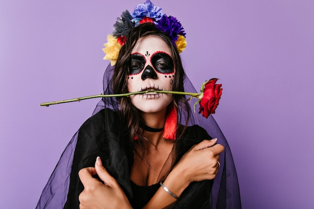 ハロウィーンでポーズをとる黒いベールの悲しい死んだ花嫁。紫色の壁に立っているメキシコのフェイスペインティングで動揺した女性。
